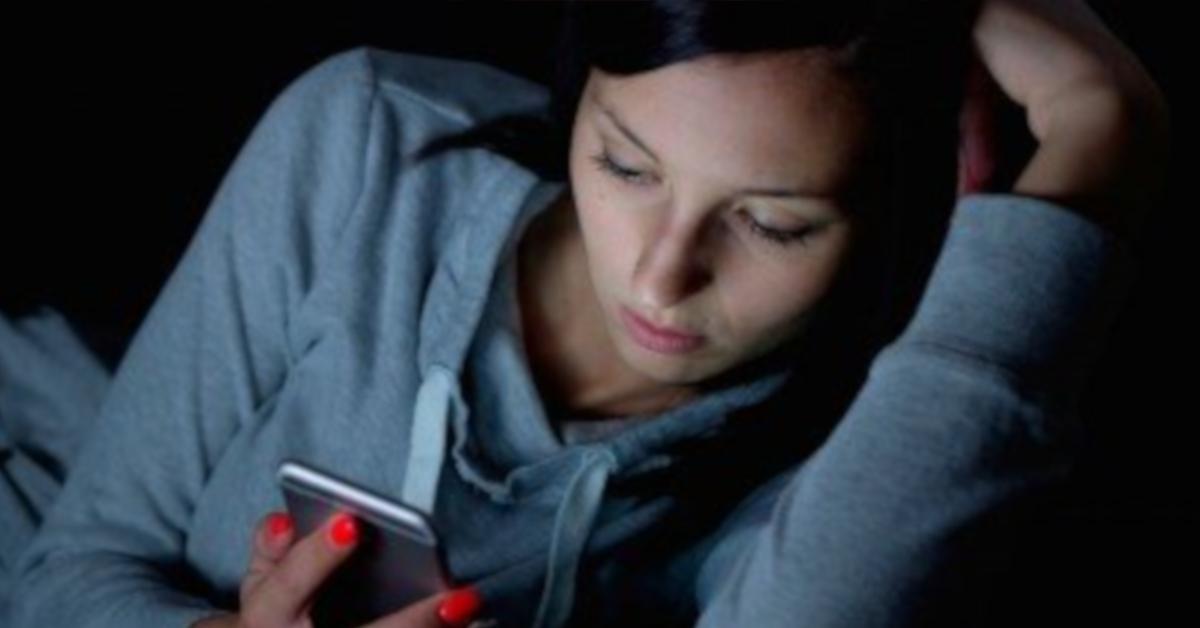 mulher triste usando celular